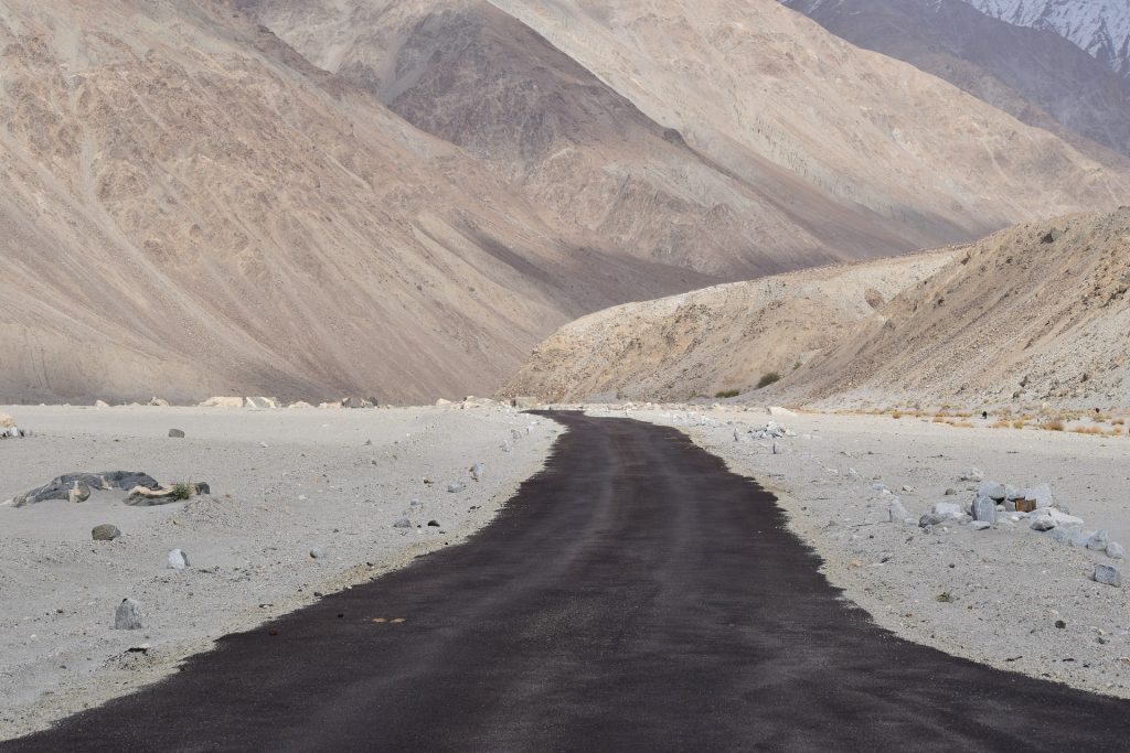road in ladakh surrounded by mountains