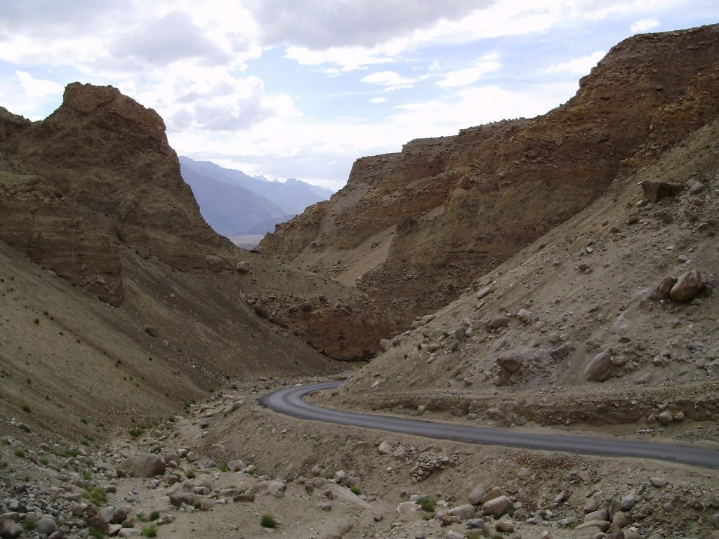 a road in Ladakh passing through rough mountains